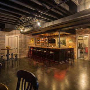 Idée de décoration pour un grand sous-sol urbain avec un bar de salon, béton au sol et un plafond en poutres apparentes.