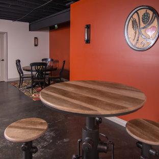 Cette photo montre un grand sous-sol industriel avec un bar de salon, béton au sol et un plafond en poutres apparentes.