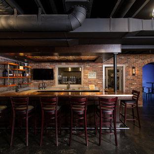 Réalisation d'un grand sous-sol urbain avec un bar de salon, béton au sol et un plafond en poutres apparentes.