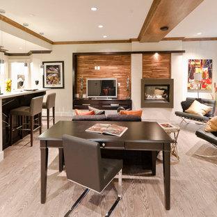 Cette photo montre un sous-sol tendance semi-enterré avec un mur blanc, un sol en bois clair, une cheminée standard, un manteau de cheminée en métal et un sol beige.
