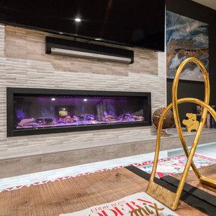 Inspiration pour un sous-sol traditionnel semi-enterré et de taille moyenne avec un mur noir, moquette, une cheminée ribbon, un manteau de cheminée en carrelage et un sol marron.