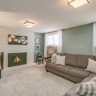 Cette photo montre un petit sous-sol chic semi-enterré avec un mur vert, moquette, une cheminée standard, un manteau de cheminée en brique et un sol gris.