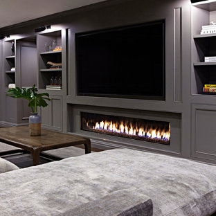 Basement - huge transitional underground dark wood floor basement idea in New York with gray walls and a ribbon fireplace