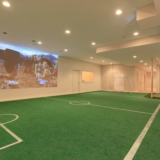 This is an example of a large traditional fully buried basement in Chicago with white walls and green floor.