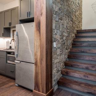 Idée de décoration pour un sous-sol chalet enterré et de taille moyenne avec un mur blanc, un sol en bois brun et un sol marron.