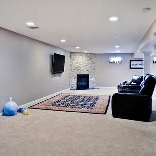 Cette photo montre un grand sous-sol chic avec un mur beige, moquette, une cheminée d'angle, un manteau de cheminée en pierre et un sol beige.