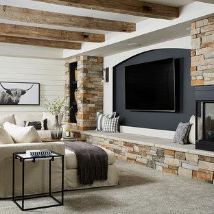 Réalisation d'un grand sous-sol champêtre donnant sur l'extérieur avec un mur gris, moquette, une cheminée double-face, un manteau de cheminée en pierre et un sol gris.