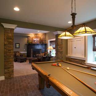 Basement - huge craftsman brick floor and gray floor basement idea in Other with green walls, a standard fireplace and a stone fireplace