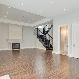 Cette photo montre un grand sous-sol semi-enterré avec un mur beige, un sol en bois foncé, un sol marron, une cheminée standard et un manteau de cheminée en béton.