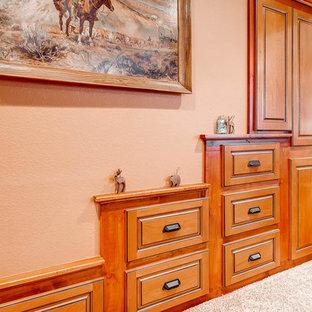 Cette photo montre un sous-sol chic donnant sur l'extérieur et de taille moyenne avec un mur beige, moquette, une cheminée double-face et un manteau de cheminée en pierre.