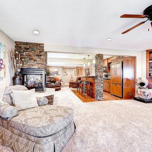 Idée de décoration pour un grand sous-sol tradition donnant sur l'extérieur avec un mur beige, moquette, une cheminée double-face, un manteau de cheminée en pierre et un sol beige.