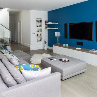 Cette photo montre un grand sous-sol tendance semi-enterré avec un mur bleu, un sol en bois brun, aucune cheminée et un sol marron.
