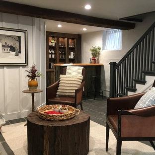 Imagen de sótano con puerta campestre, de tamaño medio, con paredes blancas, estufa de leña, marco de chimenea de piedra, suelo gris y suelo de pizarra
