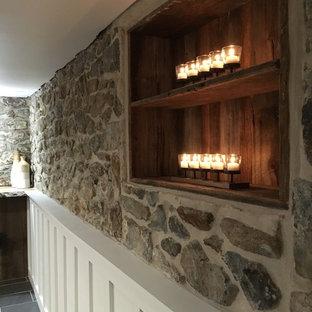 Aménagement d'un sous-sol campagne donnant sur l'extérieur et de taille moyenne avec un mur blanc, un sol en carrelage de porcelaine, un poêle à bois, un manteau de cheminée en pierre et un sol gris.