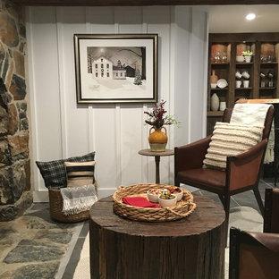 Modelo de sótano con puerta campestre, de tamaño medio, con paredes blancas, suelo de baldosas de porcelana, estufa de leña, marco de chimenea de piedra y suelo gris