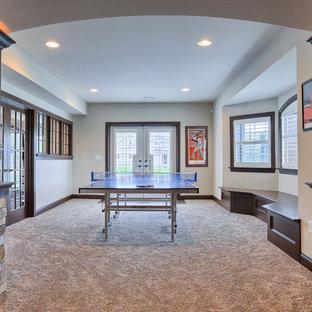 Cette image montre un très grand sous-sol traditionnel donnant sur l'extérieur avec un mur beige, moquette et un manteau de cheminée en pierre.