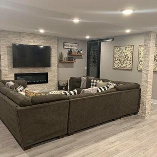 Cette image montre un sous-sol minimaliste enterré et de taille moyenne avec un mur gris, un sol en vinyl, cheminée suspendue, un manteau de cheminée en pierre et un sol gris.