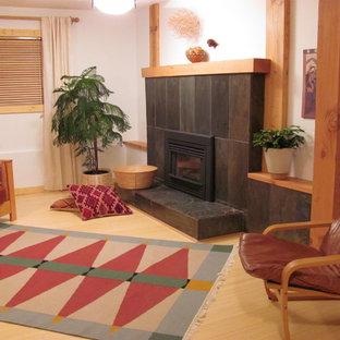 Cette image montre un sous-sol nordique de taille moyenne avec un mur blanc, un sol en bambou, une cheminée standard et un manteau de cheminée en pierre.