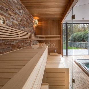 Cette photo montre un grand sous-sol tendance donnant sur l'extérieur avec un mur beige, un sol en bois brun, aucune cheminée, un manteau de cheminée en pierre et un sol beige.