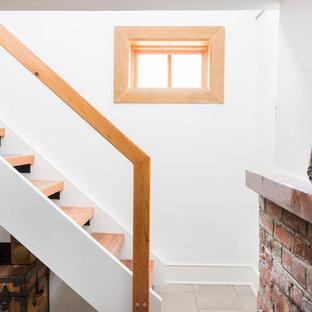Idée de décoration pour un petit sous-sol bohème semi-enterré avec un mur blanc, un sol en carrelage de porcelaine, une cheminée standard, un manteau de cheminée en brique et un sol gris.