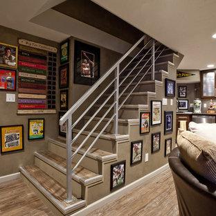 Inspiration pour un grand sous-sol traditionnel enterré avec un sol en bois brun, une cheminée standard, un mur marron et un sol marron.