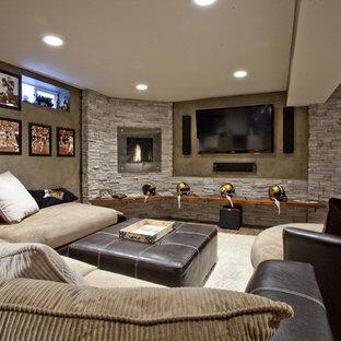 Cette image montre un grand sous-sol traditionnel enterré avec un sol en bois brun, une cheminée standard, un manteau de cheminée en métal, un mur marron et un sol marron.