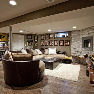 Idée de décoration pour un grand sous-sol tradition enterré avec une cheminée standard, un manteau de cheminée en métal, un mur marron, un sol en bois brun et un sol marron.