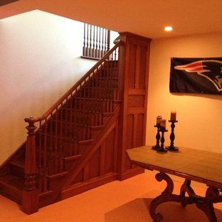 Idée de décoration pour un sous-sol tradition enterré et de taille moyenne avec un mur blanc, moquette, une cheminée standard et un sol orange.