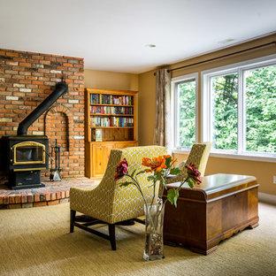 Cette photo montre un très grand sous-sol tendance donnant sur l'extérieur avec un mur beige, moquette, un poêle à bois et un manteau de cheminée en brique.