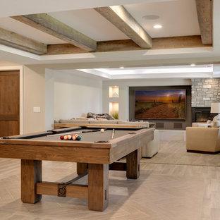 Cette image montre un sous-sol traditionnel donnant sur l'extérieur avec un mur gris, un sol en carrelage de céramique, une cheminée d'angle, un manteau de cheminée en pierre et un sol gris.