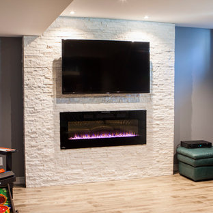 Idées déco pour un sous-sol moderne enterré et de taille moyenne avec un mur gris, une cheminée standard, un manteau de cheminée en pierre, sol en stratifié et un sol gris.