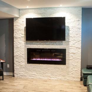 Cette image montre un sous-sol minimaliste de taille moyenne et semi-enterré avec un mur gris, une cheminée standard, un manteau de cheminée en pierre, sol en stratifié et un sol beige.