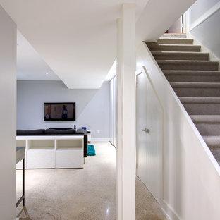 Aménagement d'un petit sous-sol contemporain enterré avec un mur bleu, béton au sol et aucune cheminée.