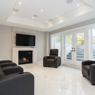 Aménagement d'un grand sous-sol classique donnant sur l'extérieur avec un mur gris, un sol en marbre, une cheminée standard, un manteau de cheminée en pierre et un sol blanc.