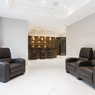 Idées déco pour un grand sous-sol classique donnant sur l'extérieur avec un mur gris, un sol en marbre, une cheminée standard, un manteau de cheminée en pierre et un sol blanc.