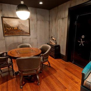 Idée de décoration pour un sous-sol tradition enterré et de taille moyenne avec un mur gris, un sol en bois brun, aucune cheminée et un sol orange.