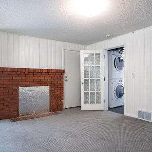 Idées déco pour un sous-sol rétro semi-enterré et de taille moyenne avec un mur blanc, moquette, une cheminée standard, un manteau de cheminée en brique, un sol gris et du lambris de bois.