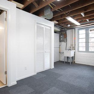 Cette image montre un sous-sol vintage semi-enterré et de taille moyenne avec un mur blanc, moquette, une cheminée standard, un manteau de cheminée en brique, un sol gris et un mur en parement de brique.