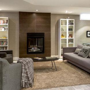 Idée de décoration pour un sous-sol design semi-enterré avec un mur gris, une cheminée standard, un manteau de cheminée en carrelage et un sol en carrelage de céramique.