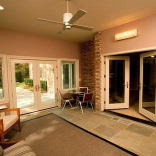 Foto di una taverna minimal di medie dimensioni con pavimento in ardesia, sbocco, pareti rosa e nessun camino