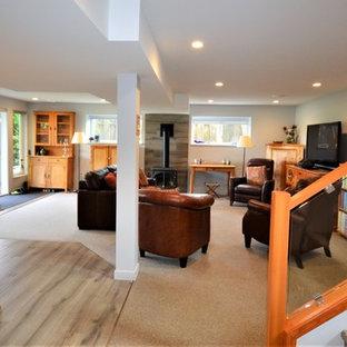 Inspiration pour un grand sous-sol traditionnel donnant sur l'extérieur avec un mur gris, moquette, un poêle à bois, un manteau de cheminée en carrelage et un sol gris.