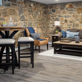 Idées déco pour un petit sous-sol campagne enterré avec un mur marron, sol en stratifié, une cheminée standard, un manteau de cheminée en pierre et un sol gris.