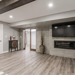 Inspiration pour un grand sous-sol traditionnel semi-enterré avec un mur gris, un sol en vinyl, cheminée suspendue, un manteau de cheminée en béton et un sol marron.