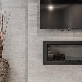 Idées déco pour un grand sous-sol classique semi-enterré avec un mur gris, un sol en vinyl, cheminée suspendue, un manteau de cheminée en béton et un sol marron.