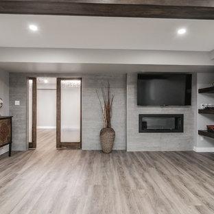 Aménagement d'un grand sous-sol classique semi-enterré avec un mur gris, un sol en vinyl, cheminée suspendue, un manteau de cheminée en béton et un sol marron.