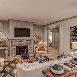 Cette image montre un très grand sous-sol traditionnel donnant sur l'extérieur avec un mur gris, un sol en bois clair, une cheminée standard et un manteau de cheminée en brique.