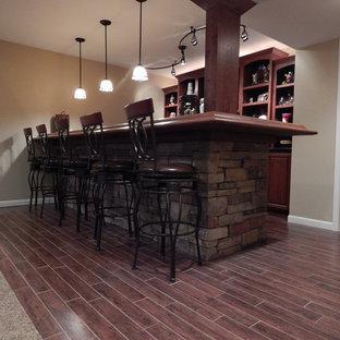 Inspiration pour un sous-sol chalet enterré et de taille moyenne avec un mur beige, un sol en bois foncé, aucune cheminée et un sol rouge.