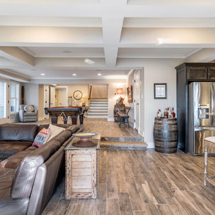 Example of a mid-sized mountain style dark wood floor and brown floor basement design in Atlanta with gray walls, a standard fireplace and a stone fireplace