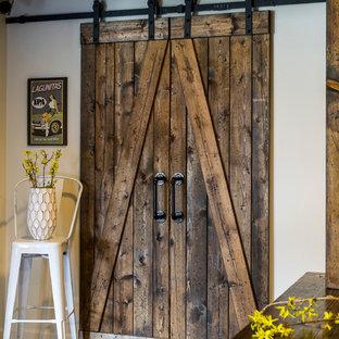 Réalisation d'un grand sous-sol champêtre donnant sur l'extérieur avec un mur blanc, un sol en bois foncé, une cheminée standard, un manteau de cheminée en brique et un sol marron.
