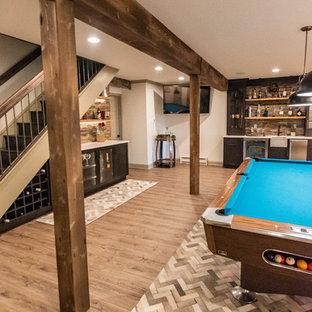 Réalisation d'un grand sous-sol chalet donnant sur l'extérieur avec un mur blanc, sol en stratifié, une cheminée d'angle, un manteau de cheminée en pierre et un sol marron.